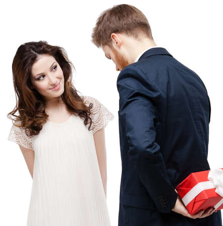 hides: Man hides the present behind the back from his pretty girlfriend, isolated on white