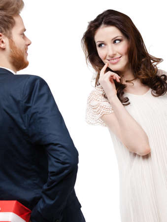 pry: Young man hides the present behind the back from his pretty girlfriend, isolated on white Stock Photo