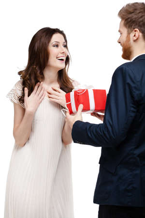 make a gift: Young man amazes his girlfriend with present, isolated on white