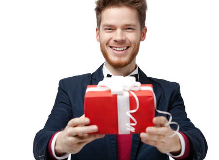 Handsome man offers a present in red box and with white bow, isolated on white Stock Photo - 17457846