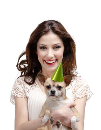 Pretty woman hugs a straw-colored small dog in cap, isolated on white photo
