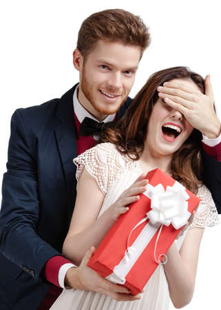 closes eyes: Man closes eyes of his girlfriend presenting a gift wrapped in red paper, isolated on white Stock Photo