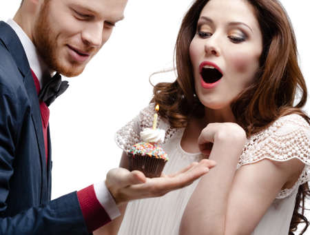 Man wonders his pretty girlfriend with birthday pie, isolated on white Stock Photo - 17457854