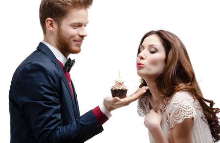 torta con candeline: L'uomo presenta spugna torta di compleanno per la sua ragazza bella, isolato su bianco