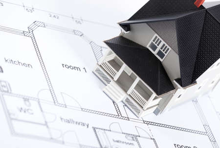 realty residence: Realty concept - construction plan with  household architectural model on it