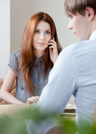 adult intercourse: Woman speaks on the mobile phone sitting with boyfriend at the cafe