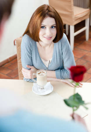 Young man presents a red rose to his girlfriend at the cafe photo