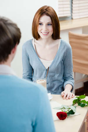 adult intercourse: Man and woman are at the cafe table with rose near them Stock Photo