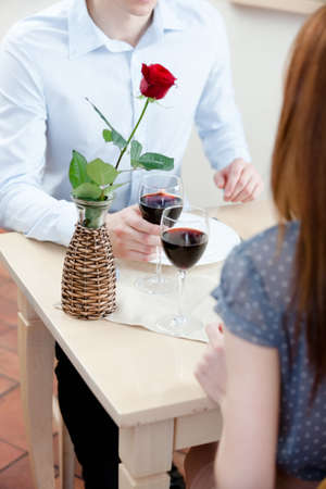 Couple is at the restaurant sitting at the table with vase and red rose in it photo
