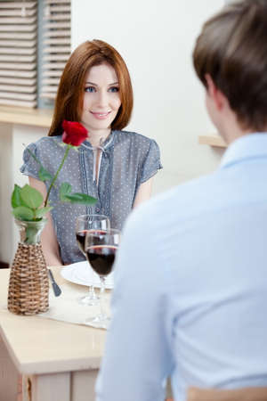 red hair woman: Couple is at the restaurant sitting at the table with vase and scarlet rose in it Stock Photo
