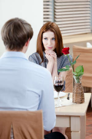 Couple is at the coffee house sitting at the table with vase and red rose in it photo