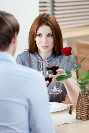 adult intercourse: Pair is at the coffee house sitting at the table with vase and crimson rose in it Stock Photo