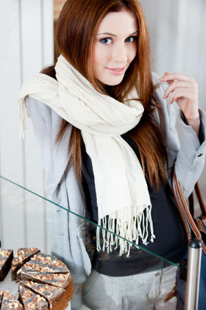 Lady in scarf looking at the bakery window full of different pieces of tarts Stock Photo - 17480632