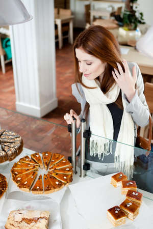 Woman in scarf looking at the bakery glass case full of different pieces of pies Stock Photo - 17480610