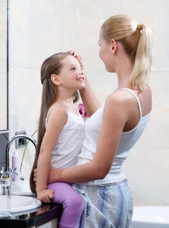 Mom and daughter are in bathroom. Mother touches head of the girl Stock Photo