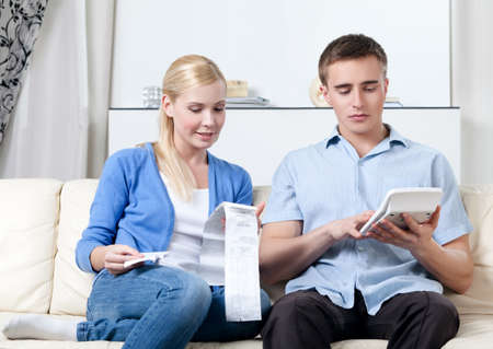 Married couple calculates the expenses sitting on the sofa