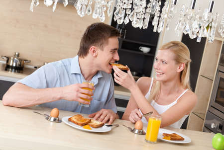 Woman feeds his husband with breakfast in the modern comfortable kitchen Stock Photo - 17480637