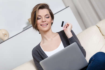 online purchase: Woman makes purchases through the internet holding credit card