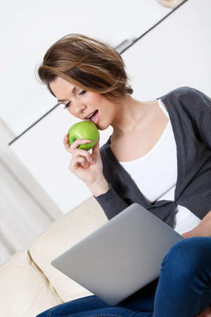 Sitting on the sofa beautiful woman eats a green apple Stock Photo - 17480618