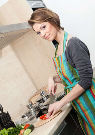 Woman in striped apron cooks vegetables in the kitchen Stock Photo - 17457874