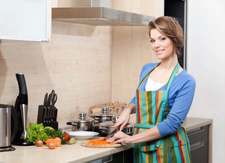 woman knife: Pretty woman in striped apron cooks in the modern comfortable kitchen