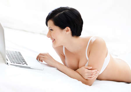 Woman in underwear is working on the silver pc while lying on the bed, isolated on white background photo