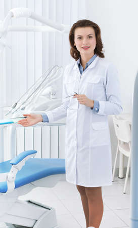 dentist drill: Beautiful doctors assistant shows the dentists chair Stock Photo