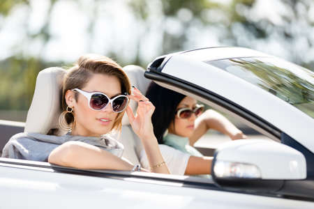 Close up view of girls wearing sunglasses in the automobile. Little holiday trip of friends Stock Photo - 17457905
