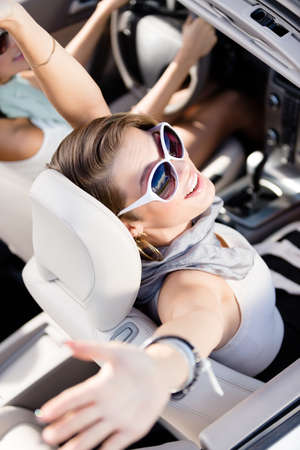 car driving: Happy girl in the car with her hands up. Having fun while driving the car Stock Photo