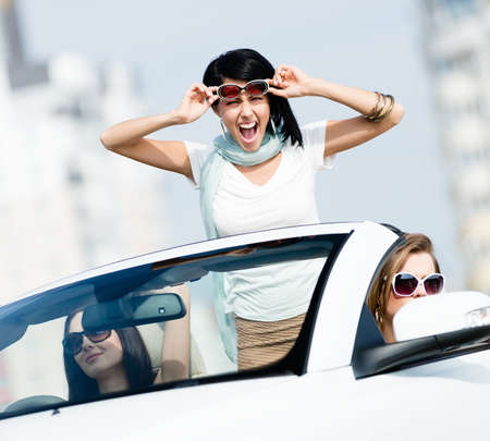Lovely teenager stands in the car with friends. Girls drive somewhere on vacation Stock Photo - 17457734