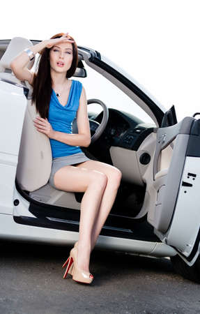 Pretty woman sits in the white car with door opened photo