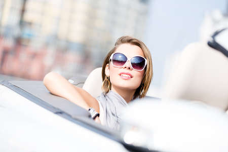 Close up of smiley woman in the cabriolet wearing cute sunglasses photo