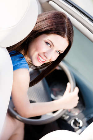 turn back: Portrait of young female driver turning back Stock Photo