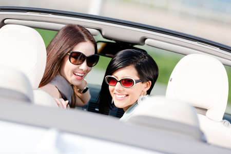 Two happy girls sitting in the car glance back and have fun while having little car trip Stock Photo - 17457897