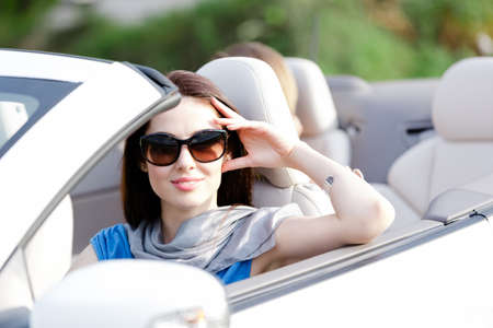 Portrait of dreamy woman wearing sunglasses in the cabriolet and propping her head Stock Photo - 17480617