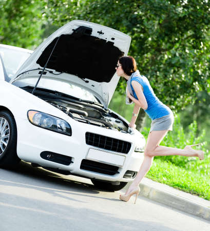 Woman opens car bonnet and tries to repair the broken car on the highway Stock Photo - 17480580