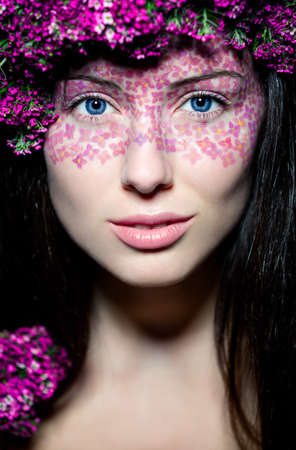 Portrait of young beautiful fresh girl with creative make-up and flowers photo