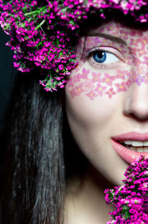 Portrait of young beautiful fresh girls half face with stylish make-up and pink flowers photo