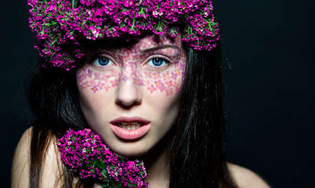 Close-up portrait of young beautiful blue-eyed woman with flowered wreath and glamorous make up photo