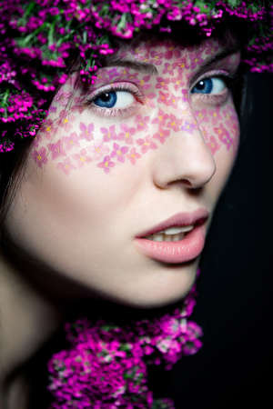 Close-up portrait of young beautiful blue-eyed woman with flowered wreath and stylish makeup photo