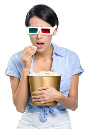 Viewer watching 3D movie in glasses with bowl full of popcorn, isolated on white photo