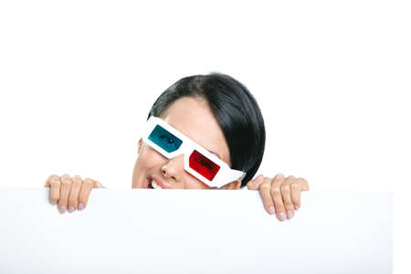 Girl in 3D glasses peeps out from behind the copyspace, isolated on white photo