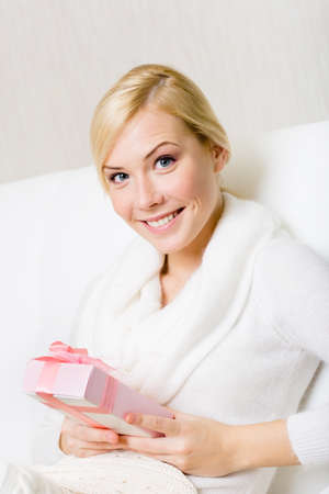 hair wrapped up: Happy woman in white sweater holds a present wrapped with pink paper and pink ribbon