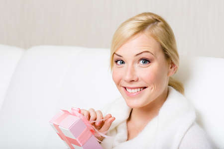 Happy woman in white sweater holds a gift wrapped with pink paper and pink ribbon photo