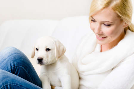 Close up of woman in white sweater with puppy of labrador sitting on her knees photo