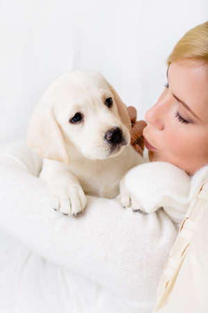 Woman in white sweater kissing white puppy of Labrador photo