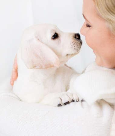 puppy love: Primer plano de la mujer en el su�ter blanco que abraza blanco cachorro