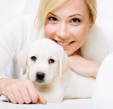 Close up of white puppy of Labrador lying on the sofa with woman in white sweater photo