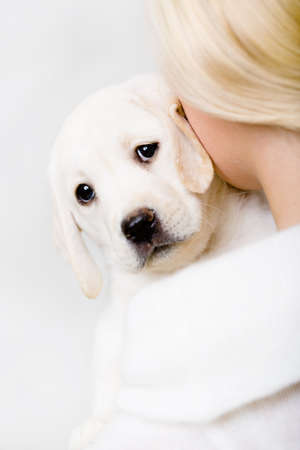 indoor shot: Back view of woman in white sweater embracing White puppy