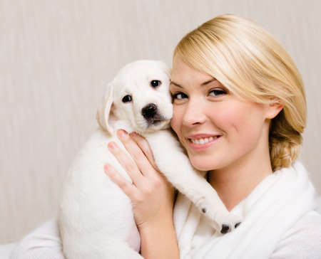 Woman keeping white labrador puppy near her face photo